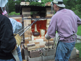 Tom Neugebauer and other artists prepare to remove raku pieces from the kiln.